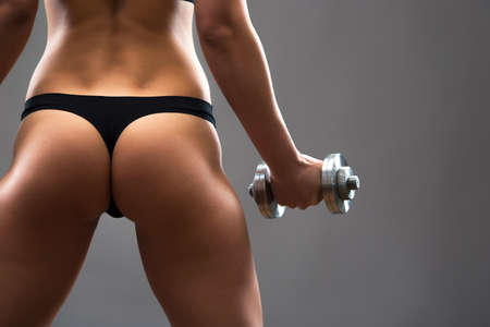 back training: Back of fitness woman. Slim woman with dumbbells.