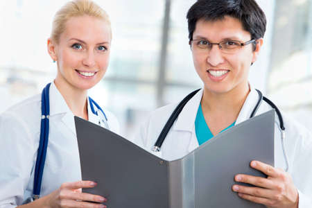concerning: Doctor giving his younger colleague a piece of advice concerning the diagnosis Stock Photo