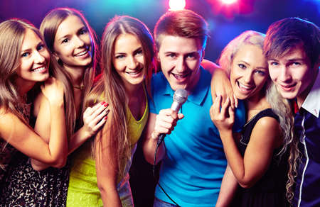 gente cantando: Los j�venes que cantan en el micr�fono en la fiesta Foto de archivo