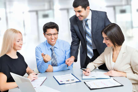 A business team of four plan work in office Imagens