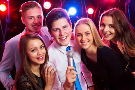 happy teenagers: Young people singing into microphone at party