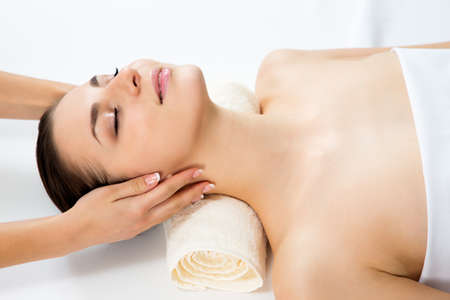 masseur: Masseur doing massage on woman face in the spa salon. Beauty treatment concept. Stock Photo