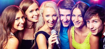 cantando: Los jóvenes que cantan en el micrófono en la fiesta Foto de archivo