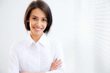 femmes souriantes: Portrait de femme asiatique d'affaires sur le fond des stores Banque d'images