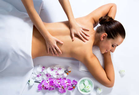 candles spa: Masseur doing massage on woman face in the spa salon. Beauty treatment concept. Stock Photo