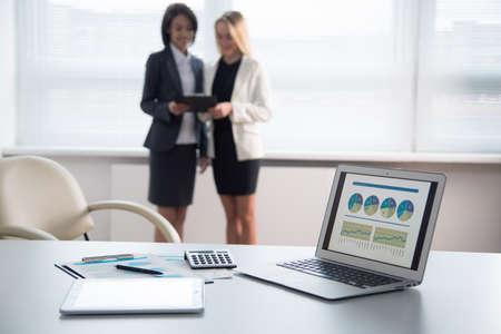 Moderne laptop op de voorgrond lege werkplek. Jonge ondernemers bespreken van plannen op de achtergrond
