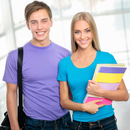 Group of happy young teenager students standing and smiling with books and bags photo