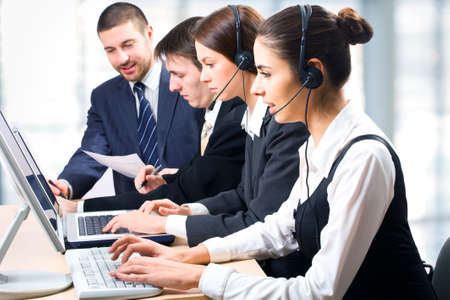 Team of people working with headsets on in a call center photo