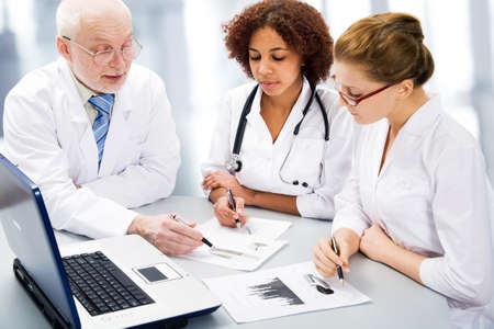 Portrait of doctor explaining computer work to coworkers photo