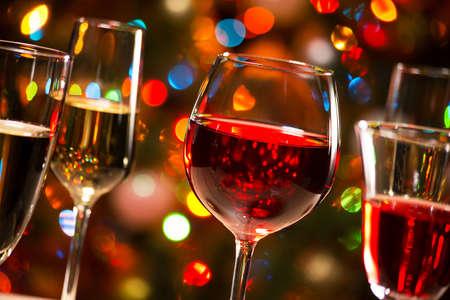 alimentos y bebidas: Vasos de cristal de vino en el fondo de las luces de Navidad