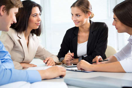 woman in office: Group of happy businesspeople in a meeting at office Stock Photo