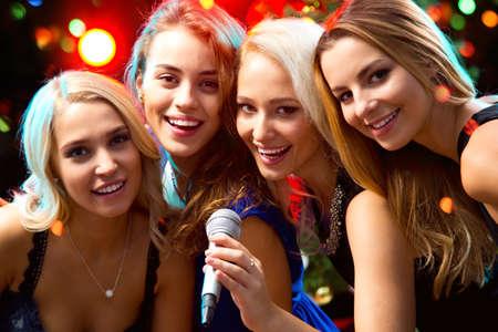 Bonne fille ayant chant amusant lors d'une fête Banque d'images - 48232159