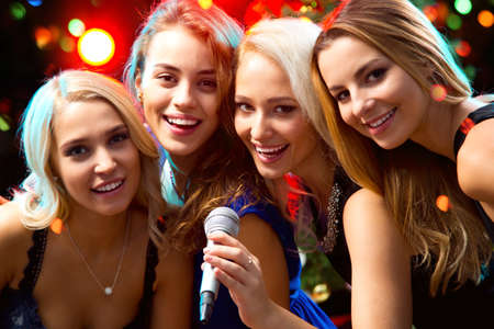 Happy girl having fun singing at a party Stock Photo - 48232159