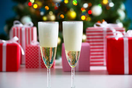 glass ornament: Glasses of champagne and Christmas gifts on the background