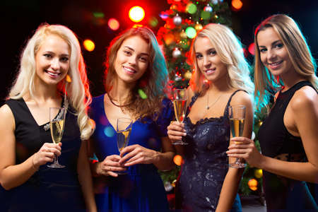 group of young people: Happy young women with glasses of champagne. Xmas Stock Photo