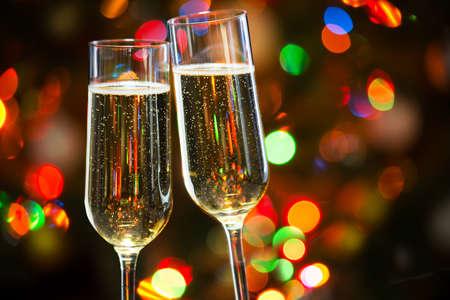 celebra: Copas de champán en el fondo de las luces de Navidad