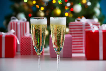 champagne: Glasses of champagne and Christmas gifts on the background