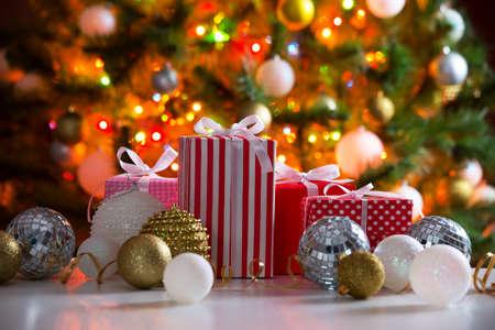 navidad elegante: Regalos de Navidad y bolas contra el telón de fondo de un árbol de navidad festivo