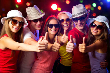 adult christmas: Happy young people show thumb up Stock Photo