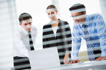 blinds: Businesspeople in a meeting at office. View through blinds Stock Photo
