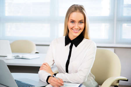 finance girl: Portrait of a young business woman using laptop at office