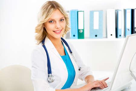 Portret van jonge vrouwelijke arts in witte jas op computer