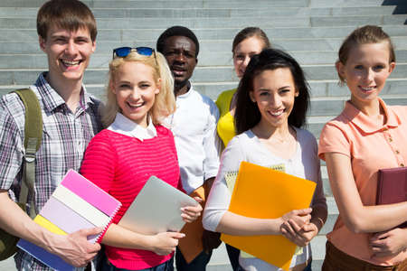 diverse students: Group of diverse students outside smiling together Stock Photo