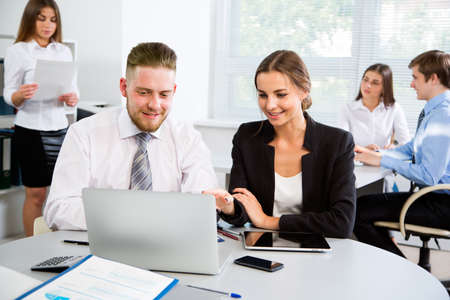 working in office: Group of happy businesspeople in a meeting at office Stock Photo