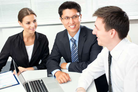 woman business suit: Group of happy businesspeople in a meeting at office Stock Photo