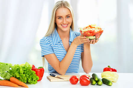 niña comiendo: Mujer joven ensalada vegetal de cocina Foto de archivo