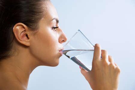 かなり若い女性は、ガラスから水を飲むのクローズ アップ 写真素材