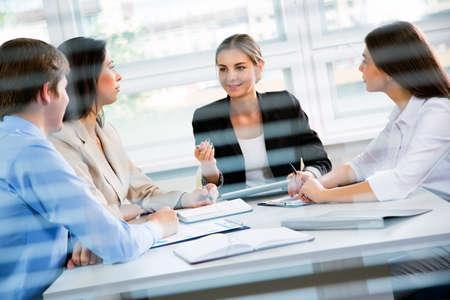 Groep van gelukkige mensen uit het bedrijfsleven in een vergadering op het kantoor van Stockfoto