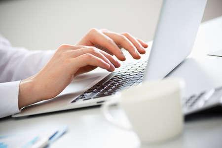 Close-up van de handen van de zakenman te typen op een laptop.