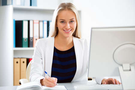 woman business suit: Young business woman with computer in the office