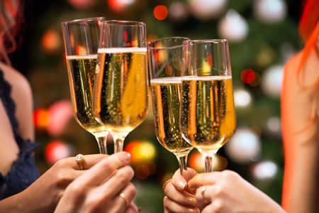 Womens hands with glasses of champagne. X-mas.