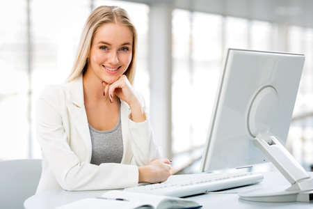 computer isolated: Portrait of a young business woman using computer at office Stock Photo