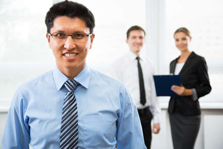 young businessman: Young businessman with colleagues in the background