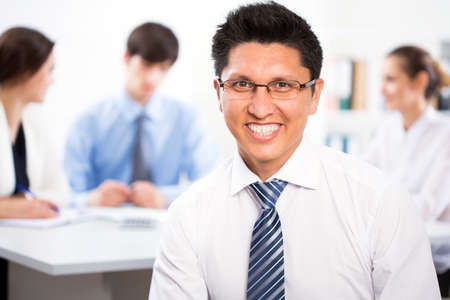 Young businessman with colleagues discussing in the background Stock Photo