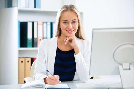 Joven empresaria con ordenador en la oficina