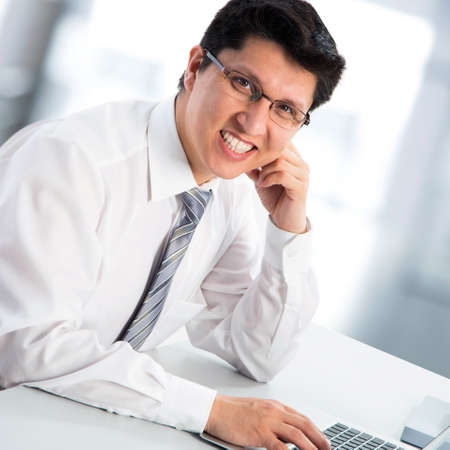 Happy business man sitting in front of laptop photo