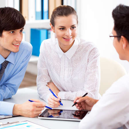 Young couple discussing terms of the loan with the bank manager photo
