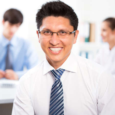 Young businessman with colleagues discussing in the background photo