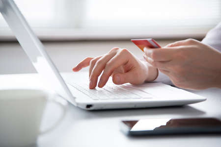 Businessman holding credit card and using laptop. Online payd. Stock Photo