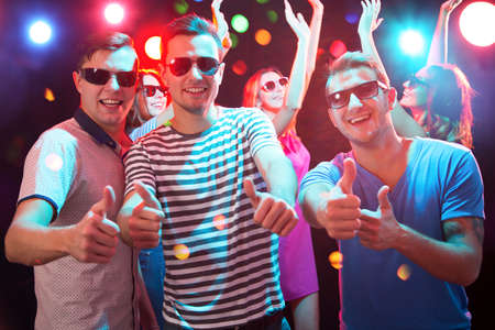 Group of happy friends showing OK sign in the night club