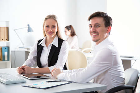 Business people are looking into the camera while working in the office Stock Photo