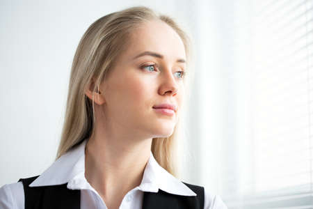 Business woman looking out the window in the office Stock Photo