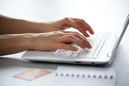 Close-up of hands of businesswoman typing on a laptop. View through blinds Stock Photo