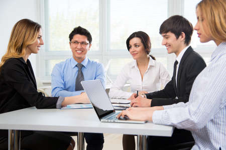 Group of business people at a meeting around a table in a modern office