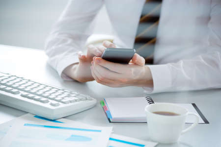Businessman holding phone and using laptop. Online payment Stock Photo
