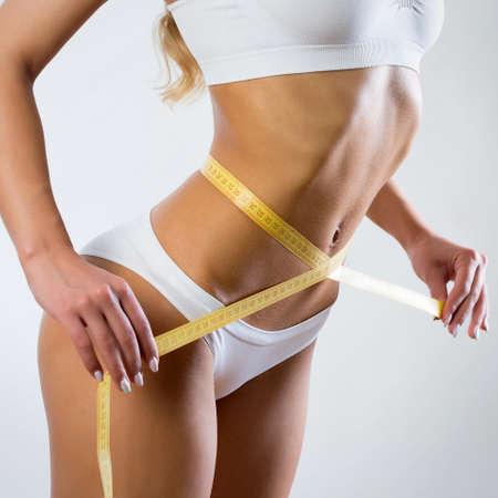 Slim beautiful woman with yellow measure